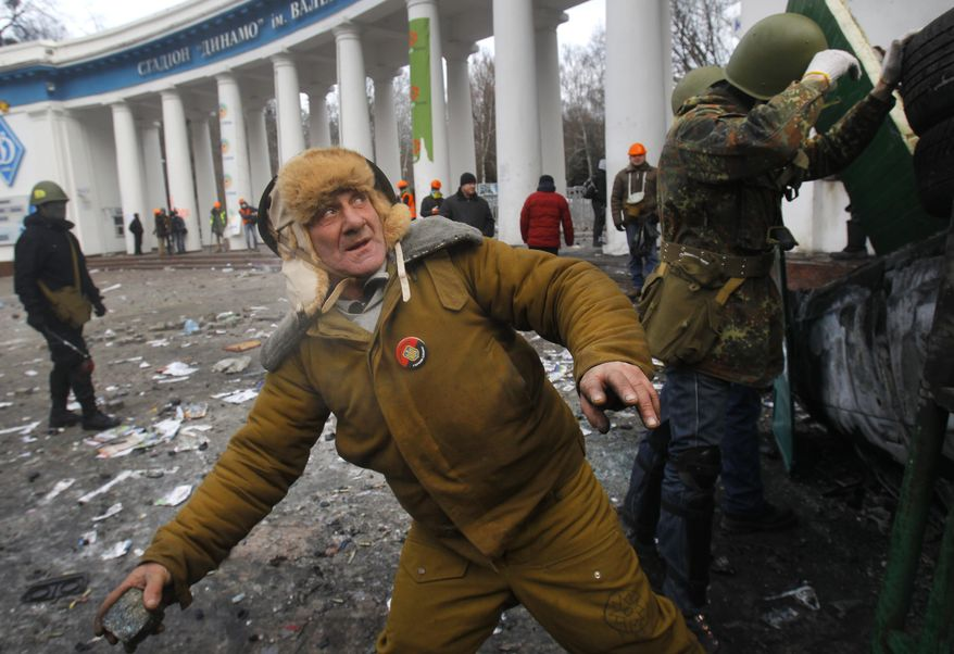 An elderly protestor prepares to throw a stone, during clashes with police, in central Kiev, Ukraine, Monday, Jan. 20, 2014. Protesters erected barricades from charred vehicles and other materials in central Kiev as the sound of stun grenades were heard in the freezing air as police tried to quell anti-government street protests. (AP Photo/Sergei Grits)