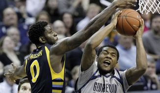 Georgetown guard D'Vauntes Smith-Rivera (4) tries to shoot past Marquette forward Jamil Wilson (0) during the second half of an NCAA college basketball game, Monday, Jan. 20, 2014, in Washington. Marquette won 80-72 in overtime. (AP Photo/Alex Brandon)