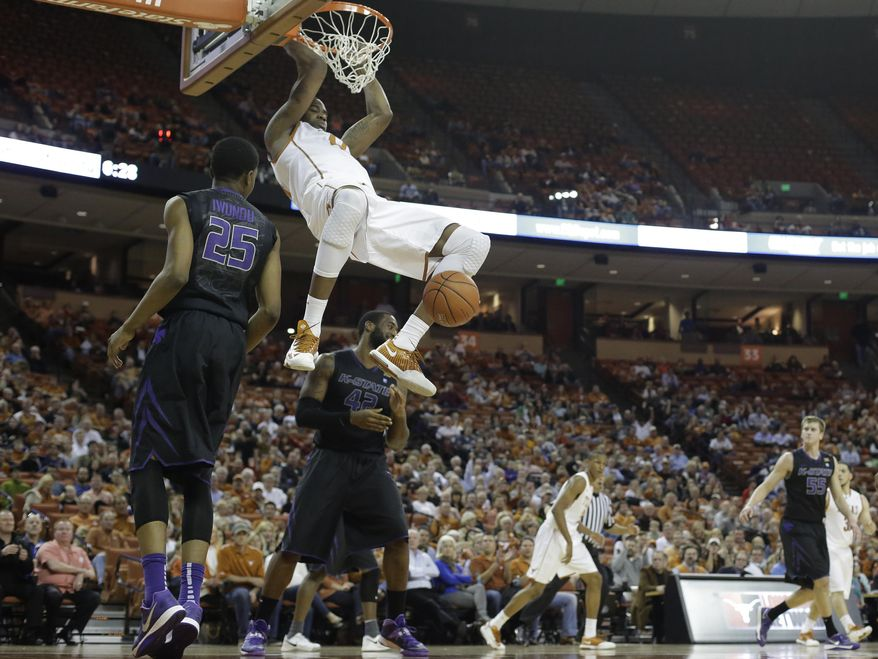 Texas' Prince Ibeh (44) scores over Kansas State's Wesley Iwundu (25) and Thomas Gipson (42)  during the first half of an NCAA college basketball game, Tuesday,  Jan. 21, 2014, in Austin, Texas. (AP Photo/Eric Gay)