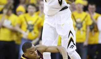 Minnesota guard Andre Hollins is fouled buy Iowa guard Devyn Marble, top, during the second half of an NCAA college basketball game, Sunday, Jan. 19, 2014, in Iowa City, Iowa. Iowa won 94-73. (AP Photo/Charlie Neibergall)