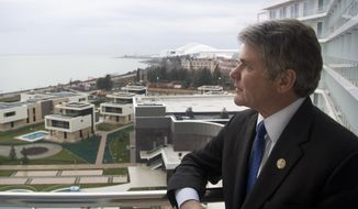 Rep. Michael McCaul, chairman of the House Homeland Security Committee, stands on the balcony of his hotel, which overlooks the Olympic Park, in the Black Sea resort of Sochi, Tuesday, Jan. 21, 2014. (AP Photo/Nataliya Vasilyeva)