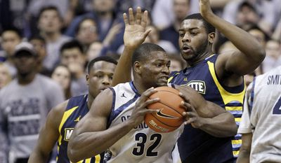 Georgetown center Moses Ayegba (32) drives against Marquette guard/forward Deonte Burton, left, and forward Davante Gardner during the first half of an NCAA college basketball game, Monday, Jan. 20, 2014, in Washington. (AP Photo/Alex Brandon)