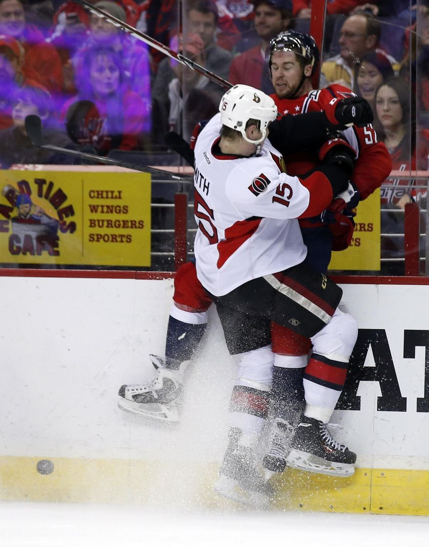 Ottawa Senators center Zack Smith (15) checks Washington Capitals defenseman Mike Green (52) in the second period of an NHL hockey game, Tuesday, Jan. 21, 2014, in Washington. (AP Photo/Alex Brandon)