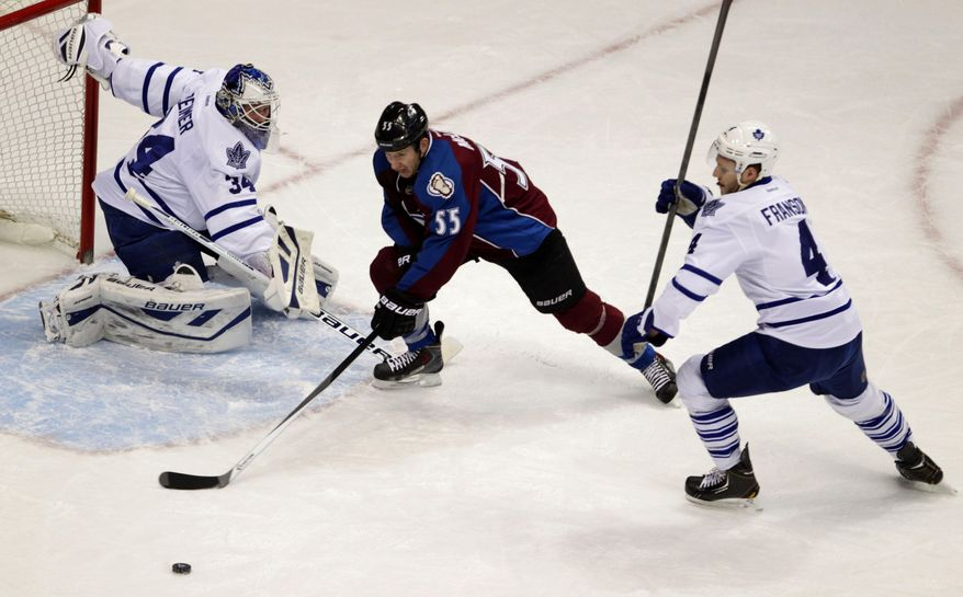 Colorado Avalanche left wing Cody McLeod (55) reaches for the puck against Toronto Maple Leafs goalie James Reimer (34) and Maple Leafs defenseman Cody Franson (4) during the second period of an NHL game in Denver on Tuesday, Jan. 21, 2014.(AP Photo/Joe Mahoney)