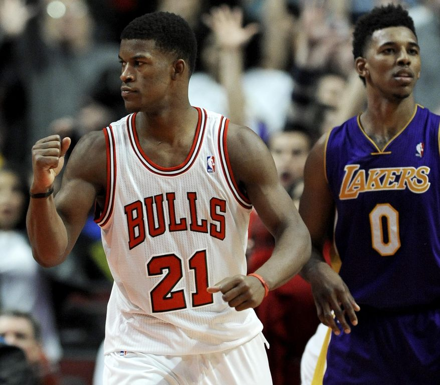 Chicago Bulls' Jimmy Butler (21), celebrates while Los Angeles Lakers' Nick Young (0) looks on after Taj Gibson made the game-winning shot in overtime to defeat the Lakers 102-100 during an NBA basketball game in Chicago, Monday, Jan. 20, 2014. (AP Photo/Paul Beaty)