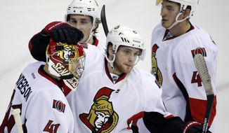 Ottawa Senators goalie Craig Anderson (41) celebrates with teammates center Kyle Turris (7), right wing Bobby Ryan (6) and defenseman Patrick Wiercioch (46) after an NHL hockey game against the Washington Capitals, Tuesday, Jan. 21, 2014, in Washington. The Senators won 2-0. (AP Photo/Alex Brandon)