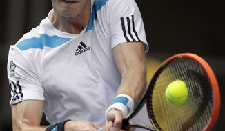 Andy Murray of Britain makes a backhand return to Stephane Robert of France during their fourth round match at the Australian Open tennis championship in Melbourne, Australia, Monday, Jan. 20, 2014.(AP Photo/Rick Rycroft)