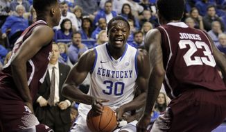 Kentucky's Julius Randle (30) looks for an opening between Texas A&M's Davonte Fitzgerald, left, and Jamal Jones (23) during the first half of an NCAA college basketball game, Tuesday, Jan. 21, 2014, in Lexington, Ky. (AP Photo/James Crisp)