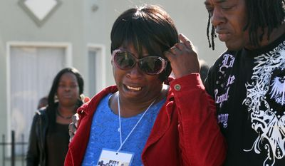 In this photo from Jan. 20, 2014, Dinyal New, center, mother of Lamar Broussard, who was killed Sunday with his best friend Derryck Harris, both 19, mourns the loss of the second son to have been killed this year, at the scene of the killing on Longfellow Avenue in Oakland, Calif. Lee Weathersby III, 13, New's other son, died on Jan. 1 after having been shot as he walked home from a New Year's Eve party. (AP Photo/The Oakland Tribune, Laura A. Oda)
