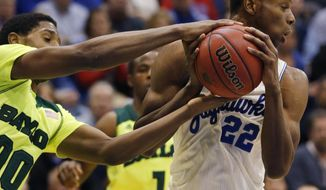 Baylor forward Royce O'Neale (00) tries to take the ball from Kansas guard Andrew Wiggins (22) during the second half of an NCAA college basketball game in Lawrence, Kan., Monday, Jan. 20, 2014. Kansas defeated Baylor 78-68. (AP Photo/Orlin Wagner)