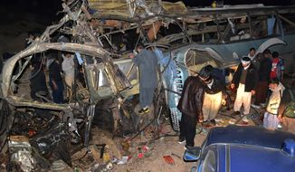 People look at the wreckage of a passenger bus destroyed in a bomb blast in the Mastong district, near Quetta, Pakistan, Tuesday, Jan. 21, 2014. A roadside car bomb hit a bus of Shiite pilgrims returning from Iran, killing several people and wounding many, in restive Baluchistan province, said a top security official. (AP Photo/Arshad Butt)