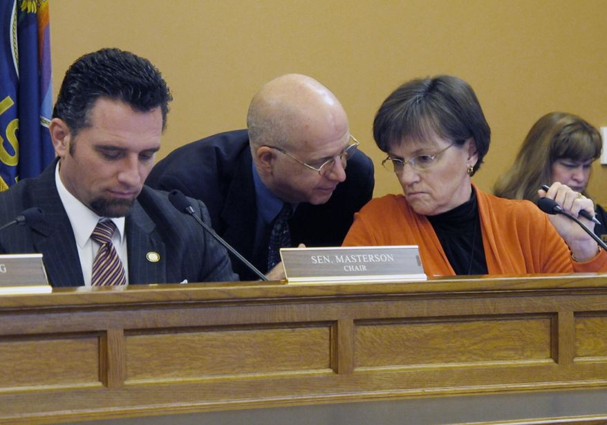 Kansas state Sen. Laura Kelly, right, a Topeka Democrat, confers with J.G. Scott, center, the top budget analyst on the Legislature's research staff, during a Senate Ways and Means Committee hearing on the prison system's budget, Tuesday, Jan. 21, 2014, at the Statehouse in Topeka, Kan. To the left, committee Chairman Ty Masterson, an Andover Republican, follows testimony. (AP Photo/John Hanna)