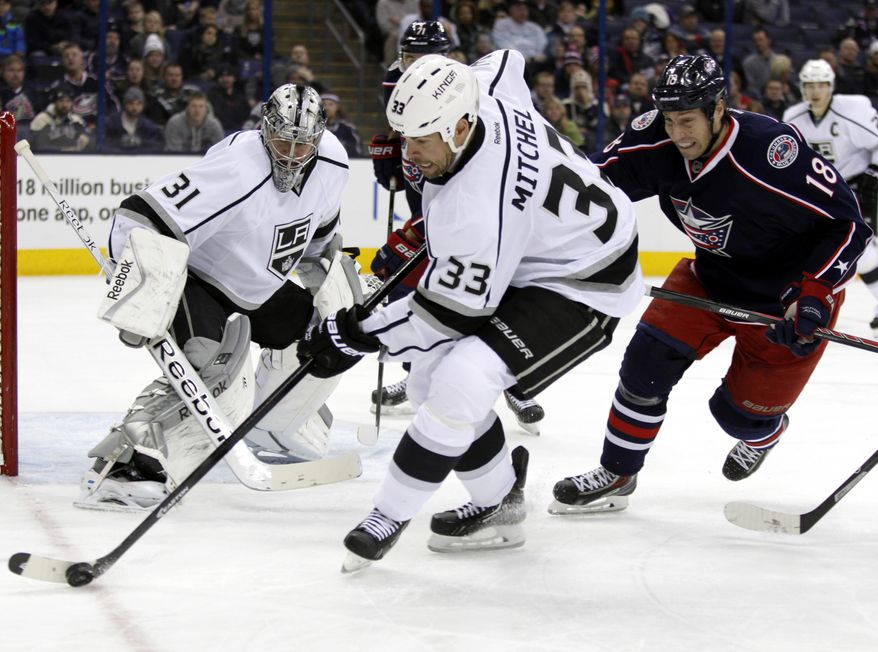 Los Angeles Kings' Willie Mitchell (33) works to clear the puck in front of teammate Martin Jones (31) and Columbus Blue Jackets' R.J. Umberger (18) in the second period of an NHL hockey game in Columbus, Ohio, Tuesday, Jan. 21, 2014. (AP Photo/Paul Vernon)