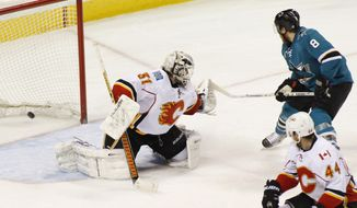 San Jose Sharks' Joe Pavelski, right, scores a goal past Calgary Flames goalie Karri Ramo during the second period of an NHL hockey game, Monday, Jan. 20, 2014 in San Jose, Calif.  (AP Photo/George Nikitin)