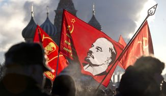 Russian Communists, carrying red flags with portrait of Soviet founder Vladimir Lenin, form a long queue as they visit the Mausoleum during Lenin's 90th death anniversary at Moscow's Red Square in Russia, Tuesday, Jan. 21, 2014. (AP Photo/Pavel Golovkin)