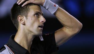 Novak Djokovic of Serbia reacts to a lost point against Stanislas Wawrinka of Switzerland during their quarterfinal at the Australian Open tennis championship in Melbourne, Australia, Tuesday, Jan. 21, 2014.(AP Photo/Rick Rycroft)