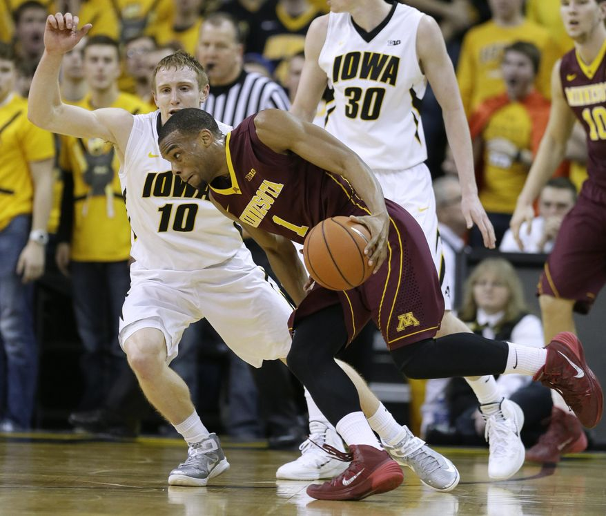 Minnesota guard Andre Hollins, right, drives past Iowa guard Mike Gesell (10) during the second half of an NCAA college basketball game, Sunday, Jan. 19, 2014, in Iowa City, Iowa. Iowa won 94-73. (AP Photo/Charlie Neibergall)