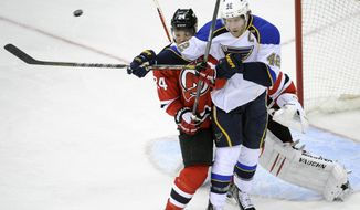 St. Louis Blues' David Backes (42) attempts to deflect the puck as he is checked by New Jersey Devils' Bryce Salvadore during the second period of an NHL hockey game Tuesday, Jan. 21, 2014, in Newark, N.J. (AP Photo/Bill Kostroun)