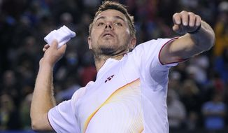 Stanislas Wawrinka of Switzerland throws a wristband to the spectators after defeating Novak Djokovic of Serbia in their quarterfinal at the Australian Open tennis championship in Melbourne, Australia, Tuesday, Jan. 21, 2014.(AP Photo/Andrew Brownbill)