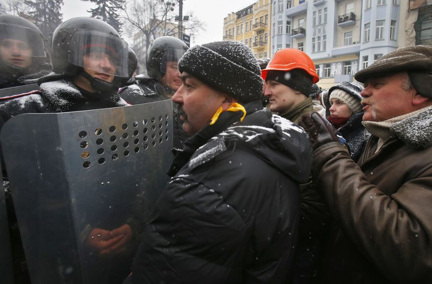 People speak to police officers as they block a street in central Kiev, Ukraine, Tuesday, Jan. 21, 2014. Opposition leader Vitali Klitschko headed for talks with the Ukrainian president on Tuesday after yet another night of violent street clashes between anti-government protesters and police. (AP Photo/Sergei Grits)
