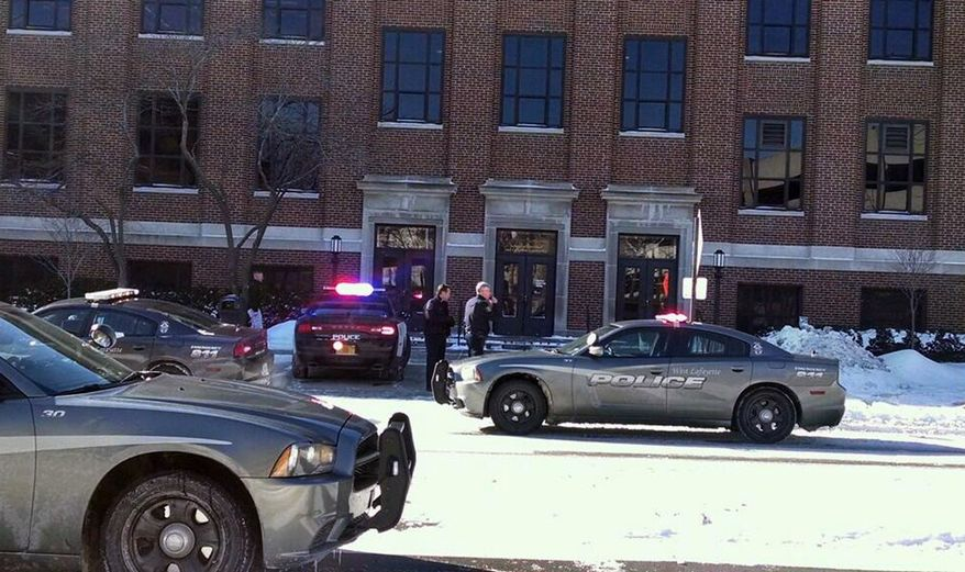 Police investigate a reports of a shooting at Purdue University in West Lafayette, Ind., on Tuesday, Jan. 21, 2014. Police say they have a person in custody and the university says it told people to take shelter and have cleared the building as the area is searched. (AP Photo/The Journal & Courier, John Terhune)
