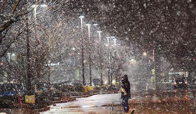 A pedestrian leaves the Target store off Durham Chapel Hill Boulevard, and walks toward the parking, during a snowy evening, Tuesday, Jan. 21, 2014 in Durham, N.C. (AP Photo/The Herald-Sun, Bernard Thomas)