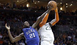Miami center Tonye Jekiri (23) recovers a rebound against Duke forward Amile Jefferson (21) during the first half of an NCAA basketball game in Coral Gables, Fla., Wednesday, Jan. 22, 2014. (AP Photo/Alan Diaz)