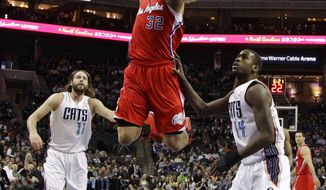 Los Angeles Clippers' Blake Griffin (32) goes in to dunk as Charlotte Bobcats' Josh McRoberts (11) and Michael Kidd-Gilchrist (14) watch during the first half of an NBA basketball game in Charlotte, N.C., Wednesday, Jan. 22, 2014. (AP Photo/Chuck Burton)