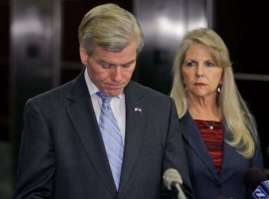 Former Virginia Gov. Bob McDonnell pauses while making a statement as his wife, Maureen, right, listens during a news conference in Richmond, Va., Tuesday, Jan. 21, 2014.  McDonnell and his wife were indicted Tuesday on corruption charges after a monthslong federal investigation into gifts the Republican received from a political donor.  (AP Photo/Steve Helber)