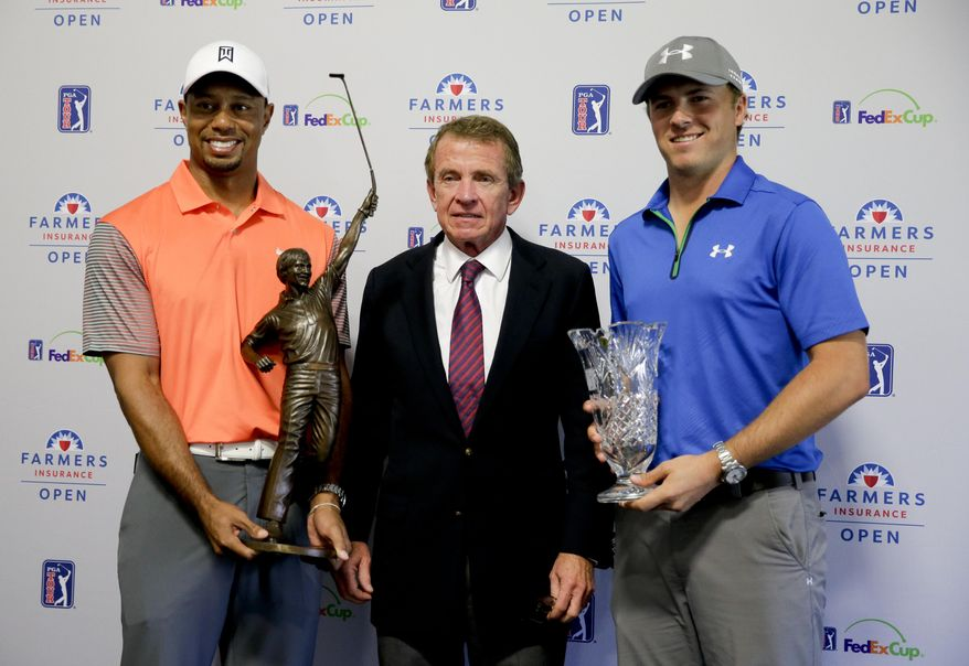 Tiger Woods, left, 2013 PGA Tour Player of the Year, and Jordan Spieth, right, PGA Tour Rookie of the Year,  pose with PGA Tour Commissioner Tim Finchem and their trophies during a presentation at the Farmers Insurance Open golf tournament at Torrey Pines Golf Course on Wednesday, Jan. 22, 2014 in San Diego. (AP Photo/Chris Carlson)