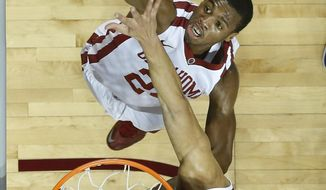 Oklahoma guard Buddy Hield (24) shoots in front of TCU forward Amric Fields during the first half of an NCAA college basketball game in Norman, Okla., Wednesday, Jan. 22, 2014. (AP Photo/Sue Ogrocki)