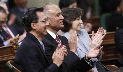 Assemblyman Ed Chau, D-Monterey Park, left, Sen. Ed Hernandez, D-Covina, center and Assemblywoman Joan Buchanan, D-Alamo, right, applaud Gov. Jerry Brown, as he gives his annual State of the State address  before a joint session of the Legislature at the Capitol in Sacramento, Calif., Wednesday, Jan. 22, 2014.  Brown delivered a dual message to lawmakers, that a California resurgence is well underway but is threatened by economic and environmental uncertainties.(AP Photo/Rich Pedroncelli)