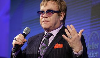"""FILE - This Oct. 30, 2013 file photo shows entertainer Elton John speaking during a panel discussion after receiving a Lifetime Achievement Award from the Rockefeller Foundation in Washington. Elton John is declaring his support of the Russian people, and he says they still accept him despite that country's harsh new anti-gay law. John said Wednesday that he visited Russia in December concerned that the new law would affect how he was treated as """"an openly gay foreigner."""" He says he received a warm welcome. (AP Photo/Alex Brandon, File)"""