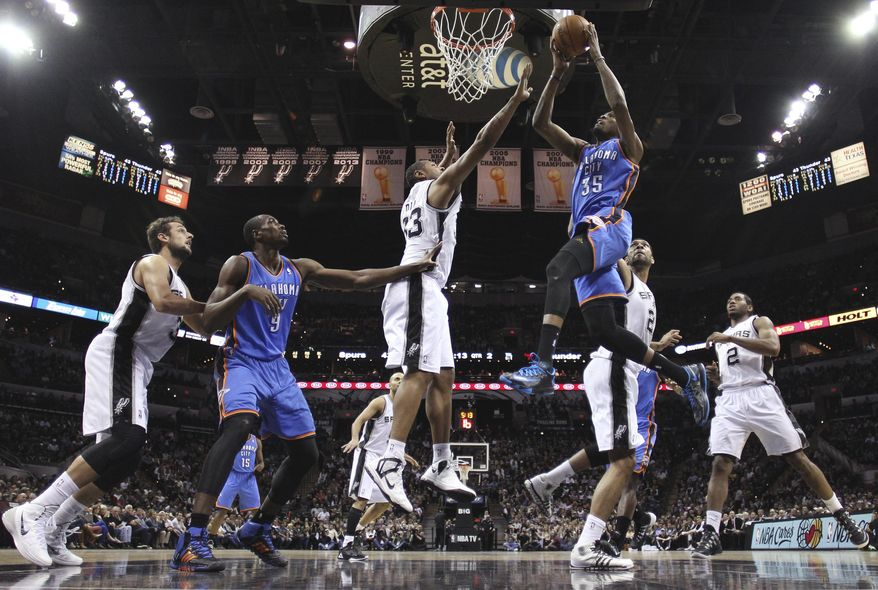 Oklahoma City Thunder's Kevin Durant (35) drives to the basket as San Antonio Spurs' Boris Diaw (33), of France, defends during the first half of an NBA basketball game, Wednesday, Jan. 22, 2014, in San Antonio. (AP Photo/Eric Gay)