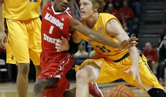 Illinois State guard Paris Lee (1) reaches in to defend against Wichita State guard Ron Baker (31) during the second half of an NCAA college basketball game at Redbird Arena, Wednesday, Jan. 22, 2014, in Normal, Ill. Wichita State won the game 70-55. (AP Photo/ Stephen Haas)