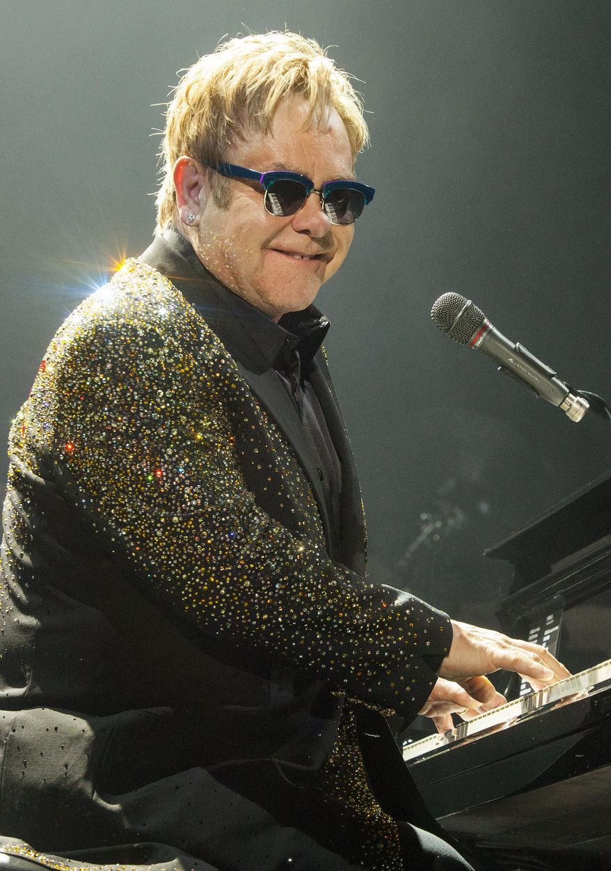 """FILE - This Nov. 30, 2013 file photo shows Elton John performing in Rosemont, Ill. Elton John is declaring his support of the Russian people, and he says they still accept him despite that country's harsh new anti-gay law. John said Wednesday that he visited Russia in December concerned that the new law would affect how he was treated as """"an openly gay foreigner."""" He says he received a warm welcome. (Photo by Barry Brecheisen/Invision/AP, File)"""