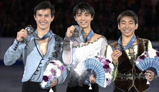 FILE - In this Friday, Dec. 6, 2013 file photo, winner Yuzuru Hanyu, center, of Japan, second-placed Patrick Chan, right, of Canada and third-placed Nobunari Oda of Japan pose for photographers after the awarding ceremony of men's event of the ISU Grand Prix Final figure skating in Fukuoka, western Japan. Hanyu's decision to shift his training base to Canada was just what the Japanese teenager needed to become a contender for the gold medal in men's figure skating at the Sochi Olympics. Moving to Toronto to train under renowned coach Brian Orser has already paid off for the 19-year-old Hanyu, who beat three-time world champion Chan at the International Skating Union's Grand Prix final in December. (AP Photo/Shizuo Kambayashi, File)