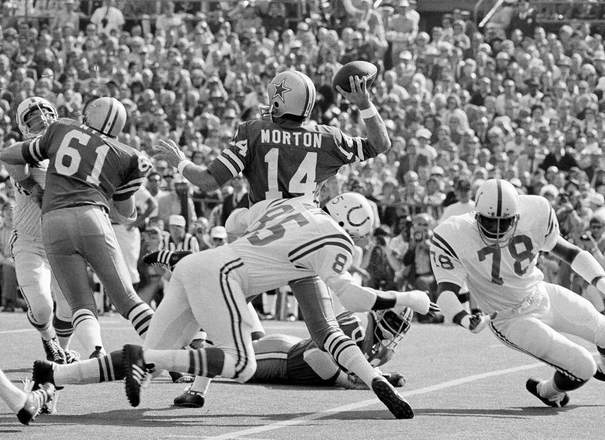 FILE - In this Jan. 17, 1971, file photo, Dallas Cowboys quarterback is hit from the rear by Baltimore Colts' Roy Hilton (85) in the first period of NFL football's Super Bowl in Miami, Fla. Peyton Manning will become only the third quarterback to start for two franchises in the Super Bowl. The first guy to do it, Morton, is among the thousands of former players suing the NFL about concussions. (AP Photo/File)