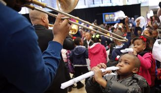 """Jared Young, 6, who made his handkerchief into a horn, pretends to play along with Glen David Andrews, left, and Irvin Mayfield as they parade through the crowd during a kick off event for the """"Turn the Page"""" literacy campaign to boost reading levels in New Orleans by 2018, the city's 300th birthday, Wednesday, Jan. 22, 2014. It was also an attempt to break the world record for the largest reading lesson. (AP Photo/The Times-Picayune, Kathleen Flynn) MAGS OUT; NO SALES; USA TODAY OUT; THE BATON ROUGE ADVOCATE OUT"""