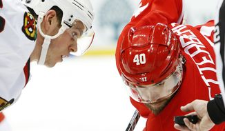 Chicago Blackhawks center Jonathan Toews, left, and Detroit Red Wings left wing Henrik Zetterberg (40), of Sweden, eye the puck on a face off in the second period of an NHL hockey game Wednesday, Jan. 22, 2014, in Detroit. (AP Photo/Paul Sancya)