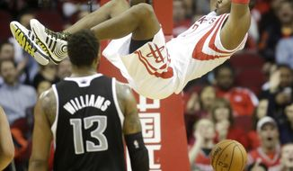 Houston Rockets guard Dwight Howard dunks the ball past Sacramento Kings forward Derrick Williams (13) during the second quarter of an NBA basketball game, Wednesday, Jan. 22, 2014, in Houston. (AP Photo/Patric Schneider)