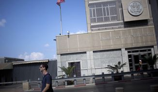 FILE--A man walks past the U.S Embassy in Tel Aviv, Israel, Sunday, Aug. 4, 2013. The threat of a terrorist attack led to the weekend closure of 21 U.S. embassies and consulates in the Muslim world and a global travel warning to Americans, the first such alert since an announcement before the 10th anniversary of the Sept. 11 strikes. (AP Photo/Ariel Schalit)