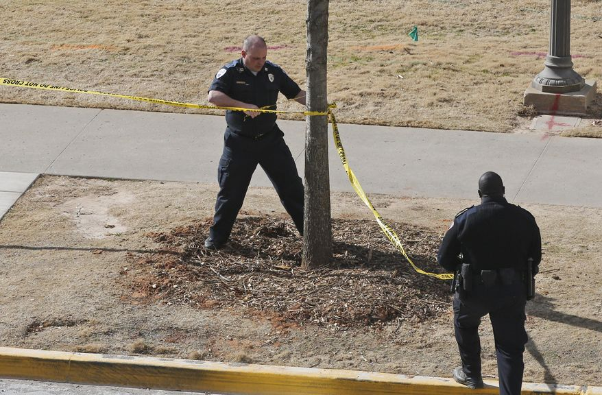 A police officers remove yellow police tape from the area surrounding Gould Hall at the University of Oklahoma in Norman, Okla., Wednesday, Jan. 22, 2014. The University of Oklahoma says authorities found no evidence of shots being fired on campus and no injuries have been reported. (AP Photo/Sue Ogrocki)