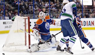 Vancouver Canucks' Kellan Lain (54) battles in front with Edmonton Oilers' Mark Arcobello (26) as goalie Ben Scrivens (30) makes the save during first period NHL hockey action in Edmonton, Canada, on Tuesday, Jan. 21, 2014. (AP Photo/The Canadian Press, Jason Franson)