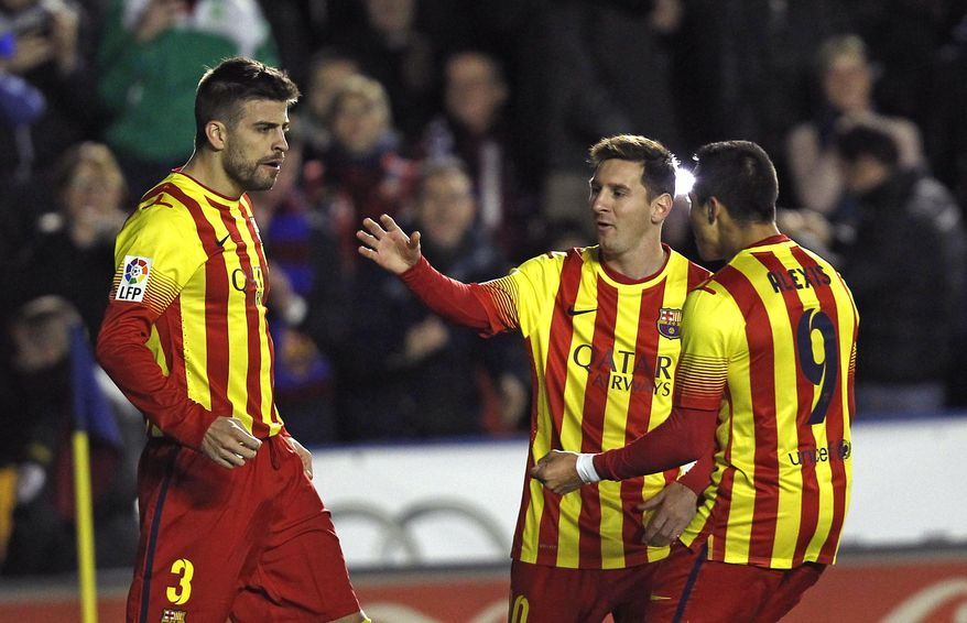 Barcelona's Gerard Pique, left, is congratulated by teammate Alexis Sanchez from Chile, and Lionel Messi from Argentina,  after  Pique scored a goal against  Levante during their La Liga soccer match at the Ciutat de Valencia stadium in Valencia, Spain, Sunday, Jan. 19, 2014. (AP Photo/Alberto Saiz)