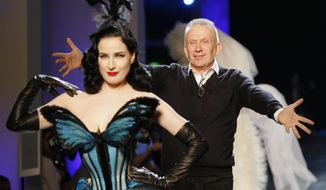 French fashion designer Jean-Paul Gaultier, right, rushes towards burlesque artist Dita Von Teese at the end of his Spring-Summer 2014 Haute Couture fashion collection, presented Wednesday, Jan. 22, 2014 in Paris. (AP Photo/Jacques Brinon)