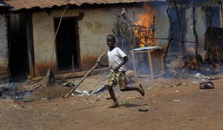 A child runs by a burning house as Anti-Balaka Christan youth loot the Muslim market in the PK13 district of Bangui, Central African Republic, Wednesday, Jan. 22, 2014. Hundreds of Anti-Balakas, helped by women and children, went on a rampage, burning and looting shops. Thirty civilian muslims, trapped inside their home, were later rescued by French forces assisted by Rwandan African Union peacekeepers. (AP Photo/Jerome Delay)