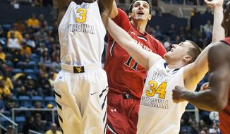 West Virginia's Juwan Staten, left, rebounds during the first half of an NCAA college basketball game against Texas Tech, Wednesday, Jan. 22, 2014, in Morgantown, W.Va. (AP Photo/Andrew Ferguson)