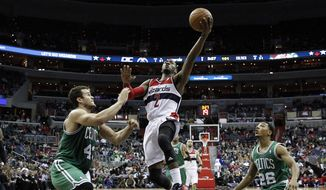 Washington Wizards guard John Wall (2) shoots between Boston Celtics center Kris Humphries (43) and guard Phil Pressey (26) in overtime of an NBA basketball game, Wednesday, Jan. 22, 2014, in Washington. Wall had 28 points, but the Celtics won 113-111, in overtime. (AP Photo/Alex Brandon)
