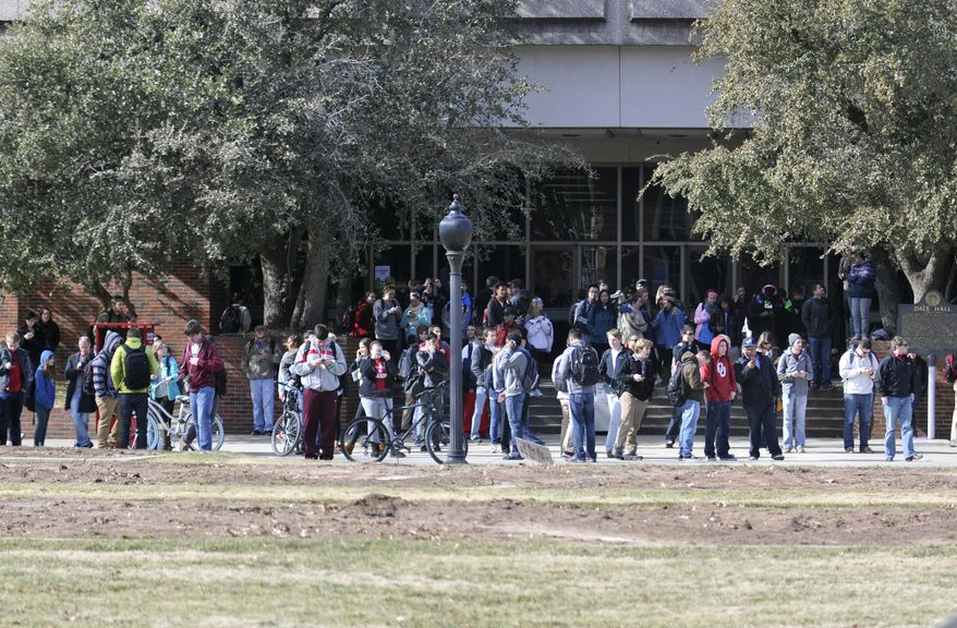 Students stand at the South Oval after being evacuated from Gould Hall as Norman and University of Oklahoma police investigate a possible shots fired call at the University of Oklahoma, Wednesday, Jan. 22, 2014, in Norman, Okla. The university was in brief lockdown. Officials said no evidence of a shooting had been found as authorities continued to sweep the building. (AP Photo/The Transcript, Kyle Phillips)